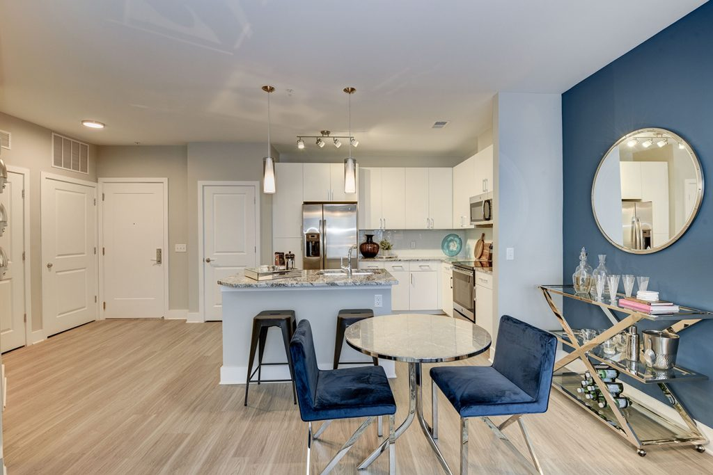 Model apartment kitchen and dining area with small table, kitchen island, and wood-style flooring