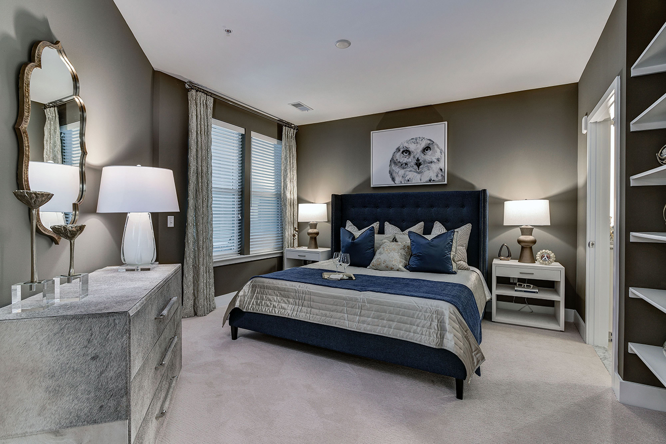 Model apartment bedroom with king-size bed, carpeted floors, and built-in bookcases