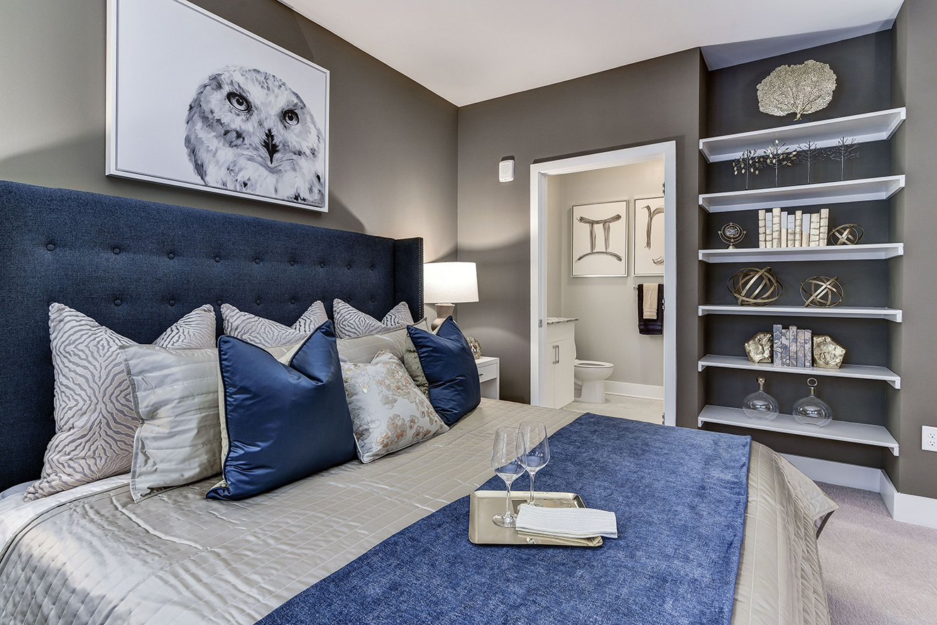Model apartment bedroom with large king-size bed, built-in bookcase, and access to ensuite bathroom