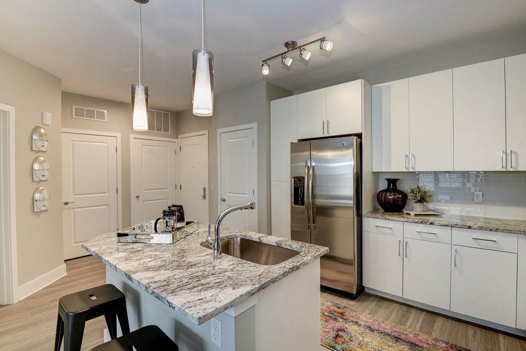 Model apartment kitchen with granite countertops, white cabinets, stainless steel appliances, and pendant lighting