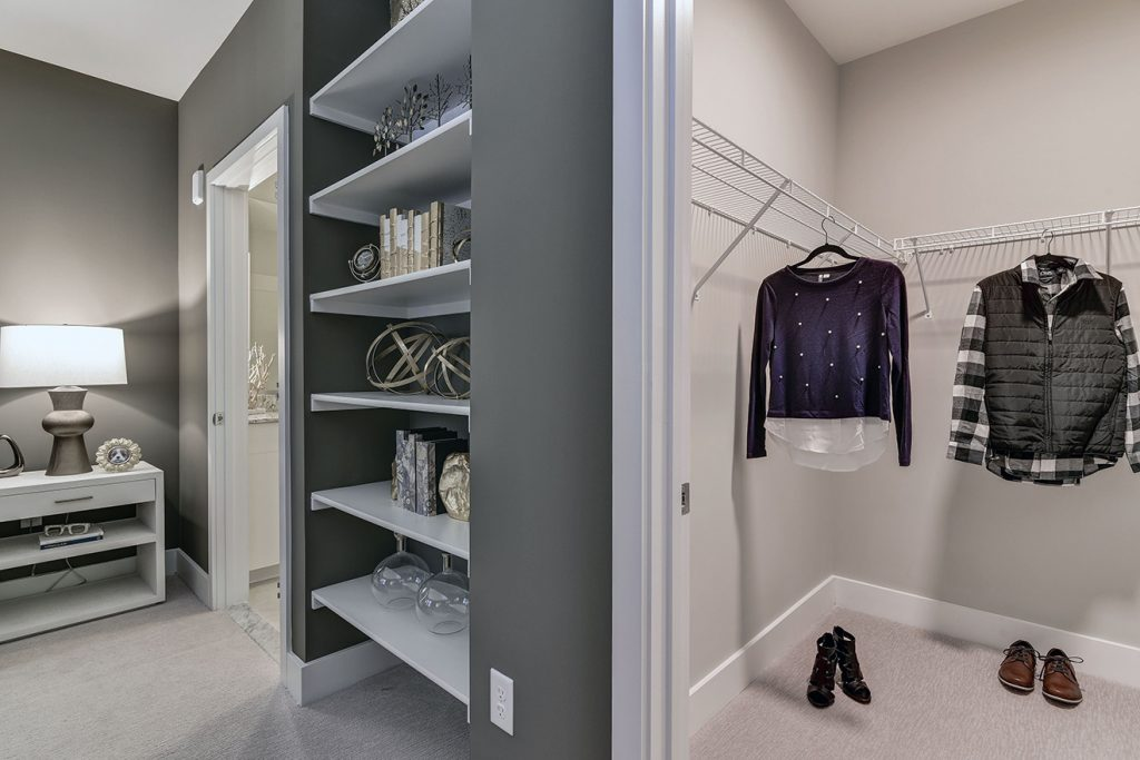 Built-in storage bookcases in model apartment bedroom near walk-in closet