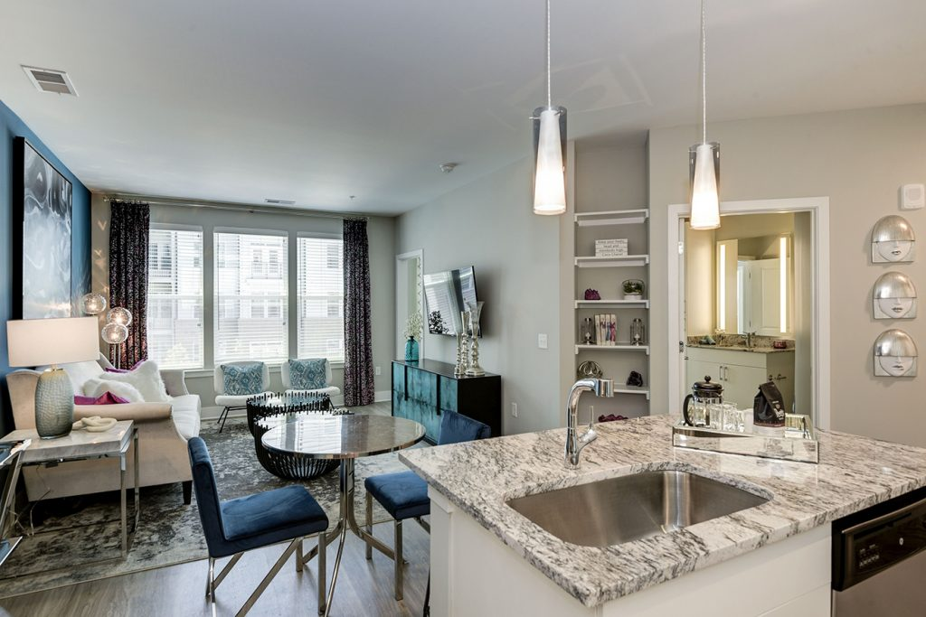 Model apartment with kitchen island, small dining set, built-in bookcase, and large windows