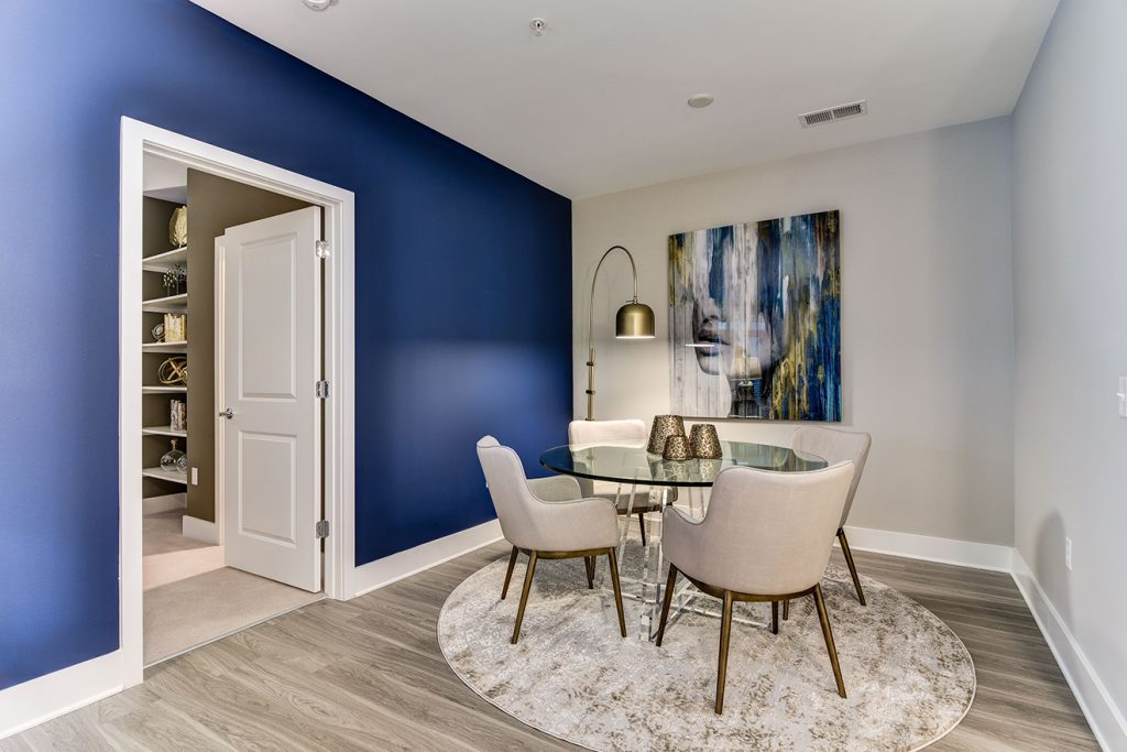 Model apartment dining area with five-piece dining set, blue accent wall, and wood-style flooring