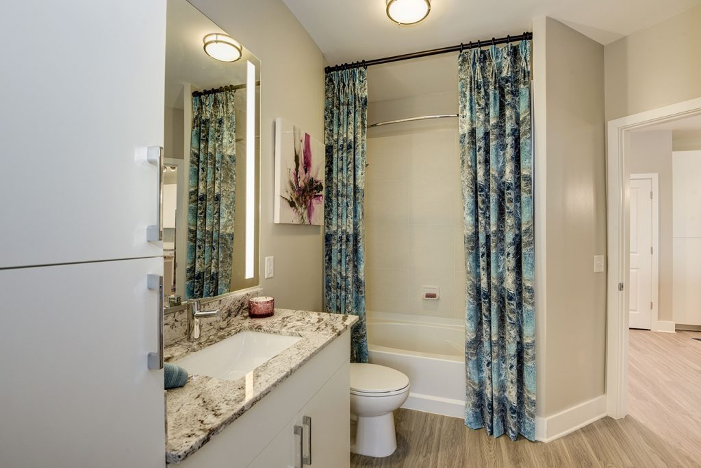 Model apartment bathroom with granite countertop, single-vanity sink, and curtained tub