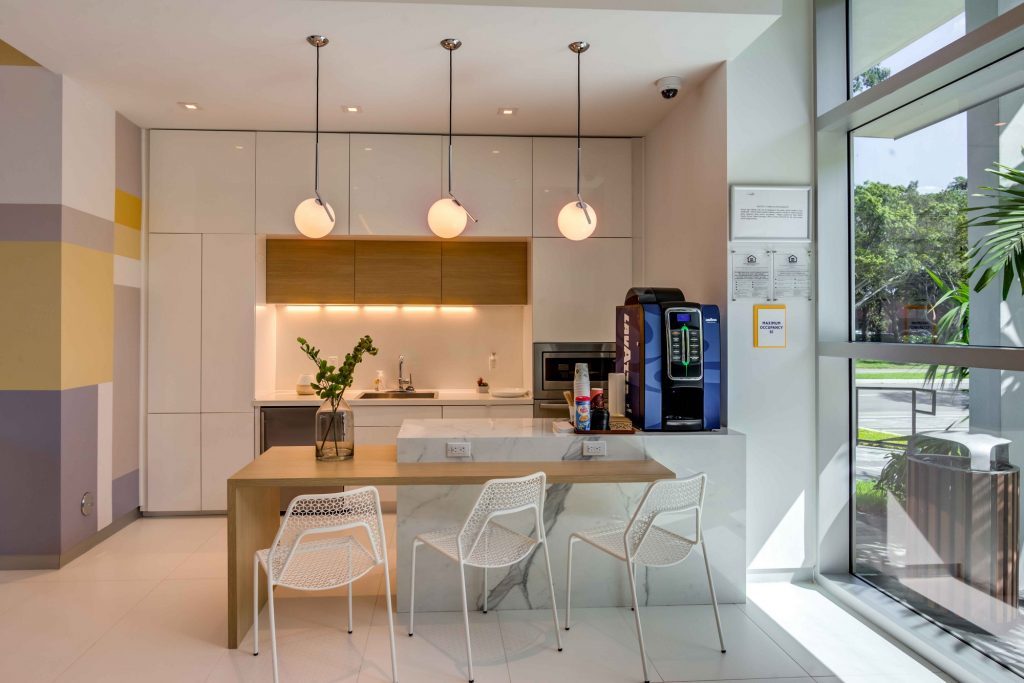 coffee bar with overhead lighting, kitchen, and bar area with seating