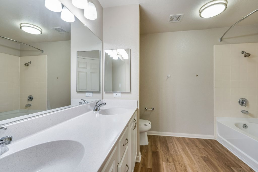Bathroom with wood flooring, large wall mirror, two sinks, and a bathtub and shower combo with curved curtain rod.