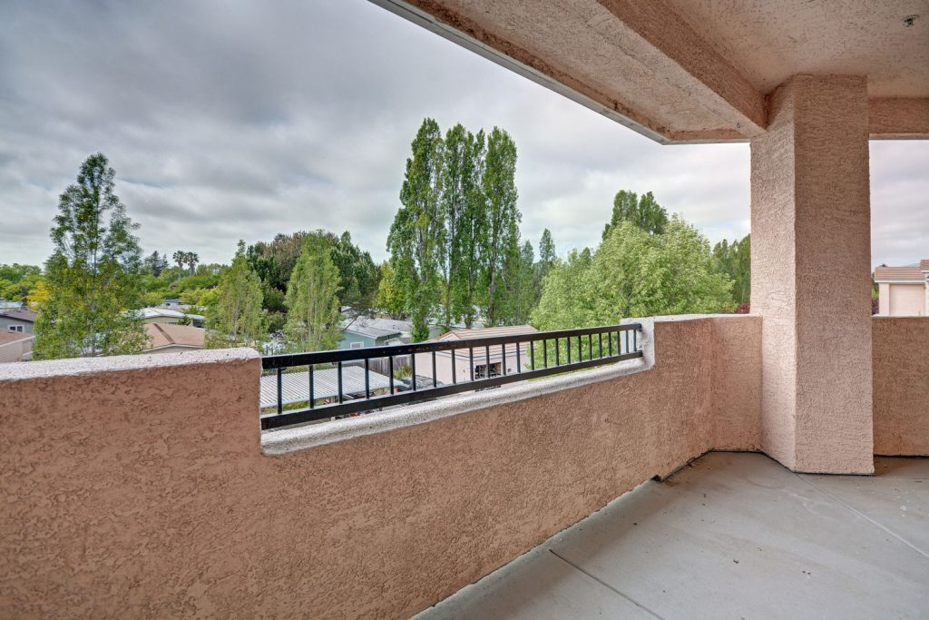 Covered apartment balcony with neighborhood and tree views