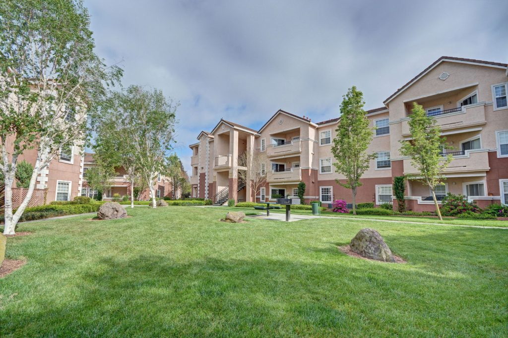 Grass courtyard between residential buildings with with lush green landscaping, picnic benches, and rock features.