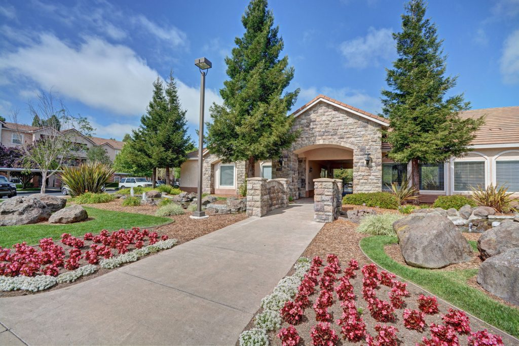 Clubhouse entrance with flowers, green landscaping, rock and water feature, and a stone bridge over water.