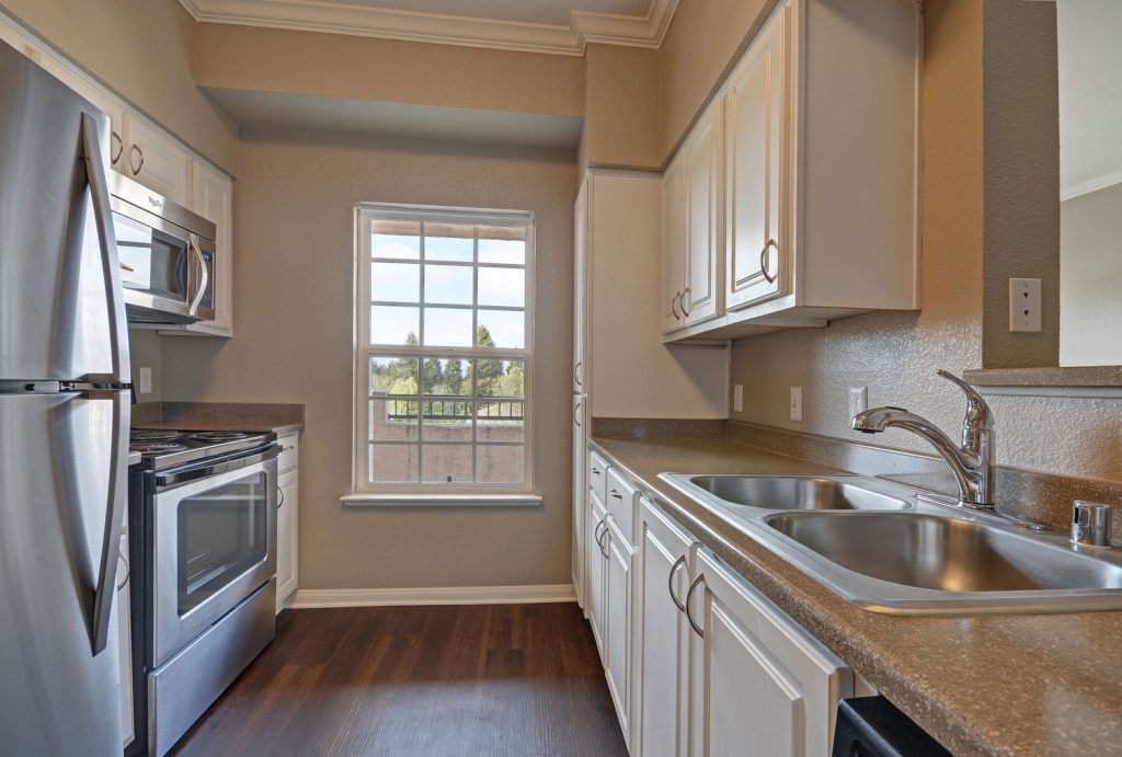 Parallel, two-wall kitchen with window, wood flooring, stainless steel appliances, two-basin sink, white cabinets, and dark countertops.