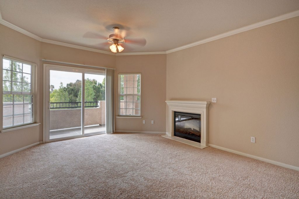 Unfurnished living room with carpet flooring, a ceiling fan, fireplace, and sliding door leading to a balcony.