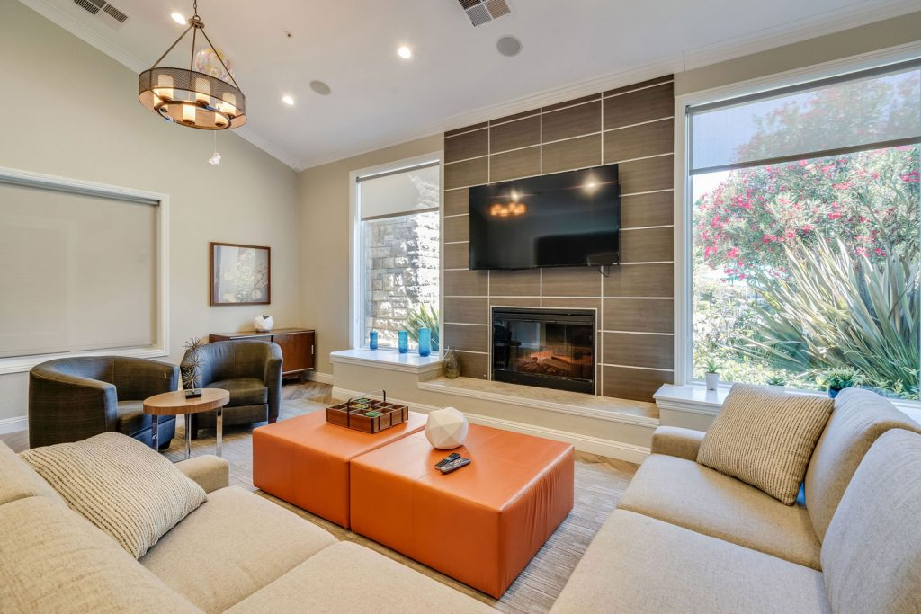 Close up of a lounge area with sectional sofa, chairs, ottoman, and a fireplace with a large wall mounted TV above.