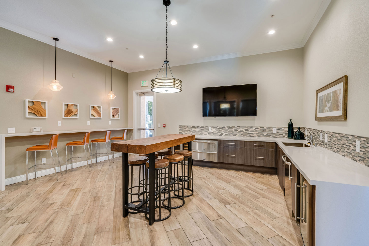 Community kitchen with island and barstool seating, and a large wall mounted TV