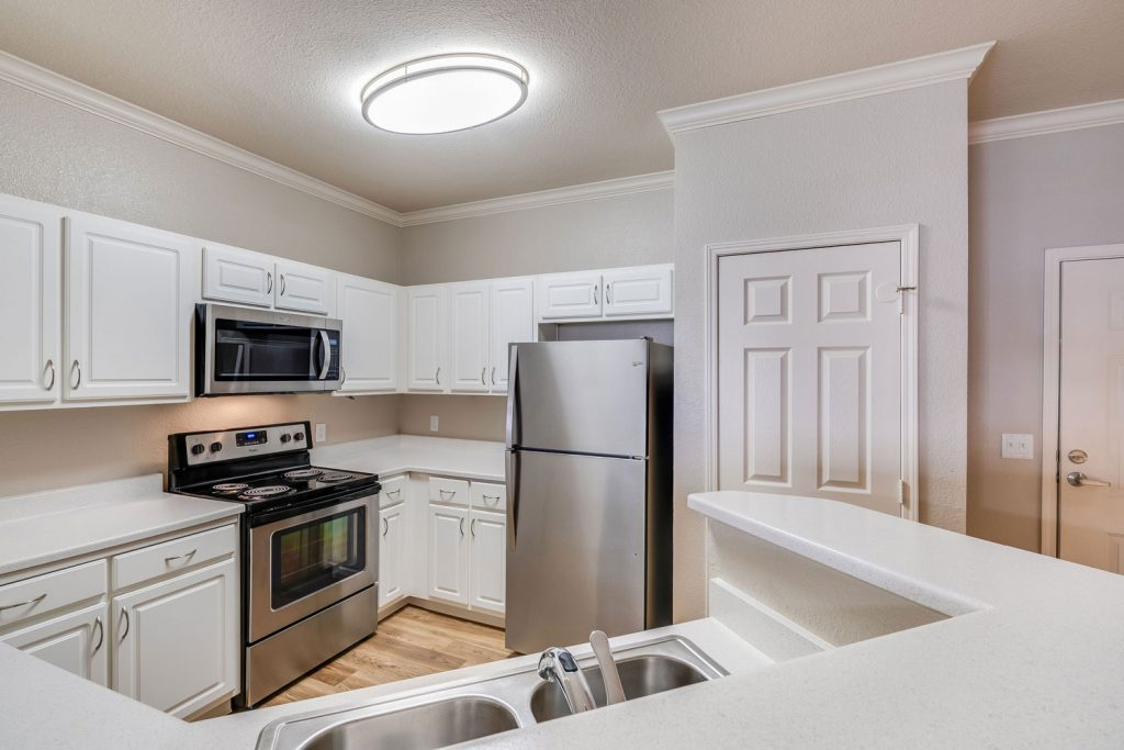 Kitchen with wood flooring, stainless steel appliances, a two-basin sink with a raised bar counter, pantry, and white countertops and cabinets.