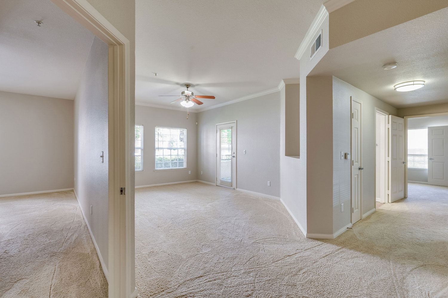 Unfurnished living room with carpet flooring, a ceiling fan, patio door, and adjacent hallway and bedroom.