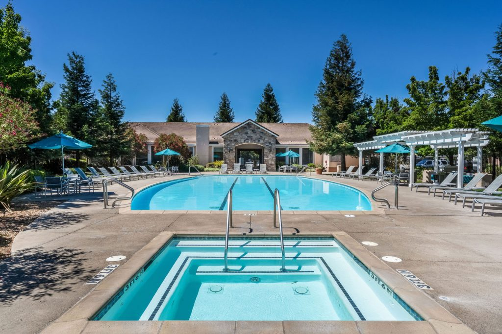 Swimming pool and spa courtyard behind the resident clubhouse with chaise lounge chairs, dining tables with umbrella coverings, and pergola shade structures.