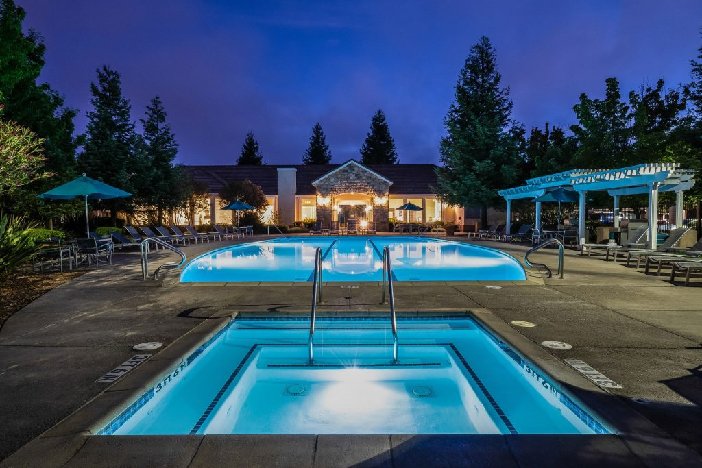Swimming pool and spa courtyard at night with glowing lights on the resident clubhouse, chaise lounge chairs, dining tables with umbrella coverings, and pergola.