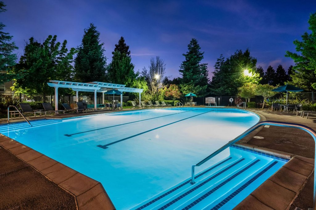 Swimming pool at night with lights, chaise lounge chairs, dining tables with umbrellas, and pergola