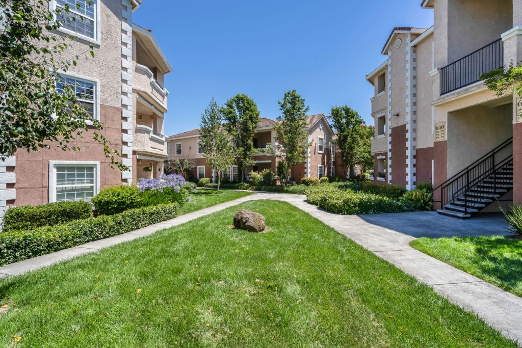 Community courtyard between residential buildings with with lush green landscaping and sidewalks.