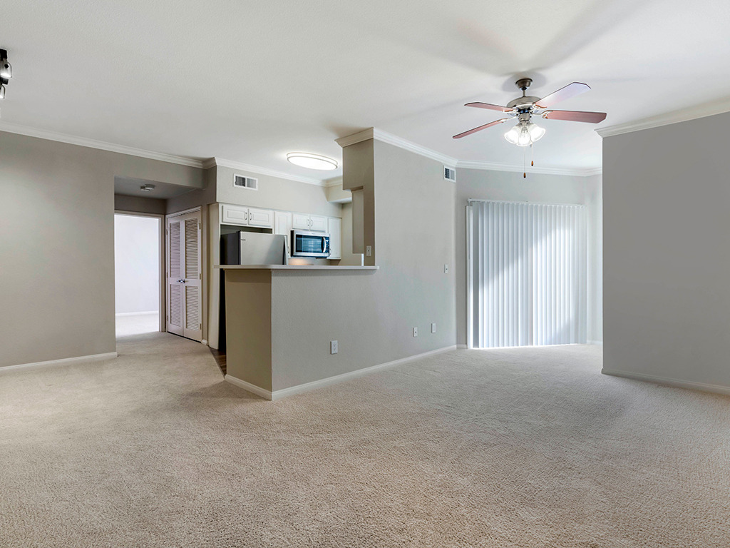 Living room area with carpet flooring, white walls, and ceiling fans, with kitchen and stainless steel appliances