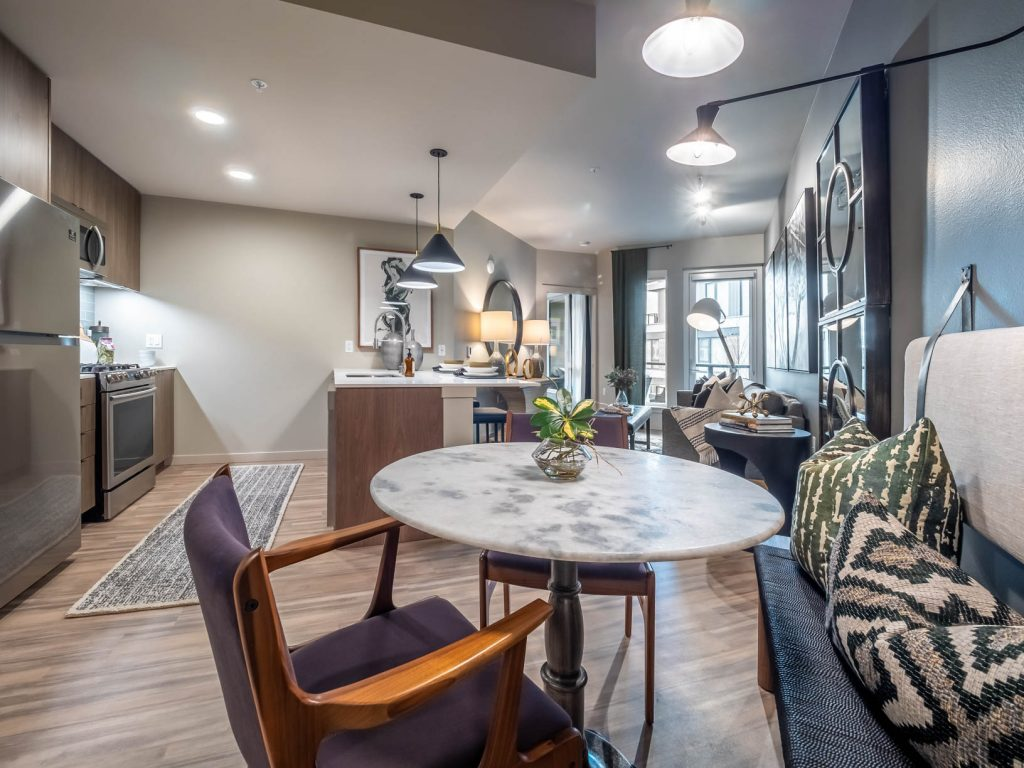 Furnished open concept apartment with a parallel style kitchen, dining area, and living room featuring wood flooring, stainless steel appliances, and pendant, recessed and track lighting.