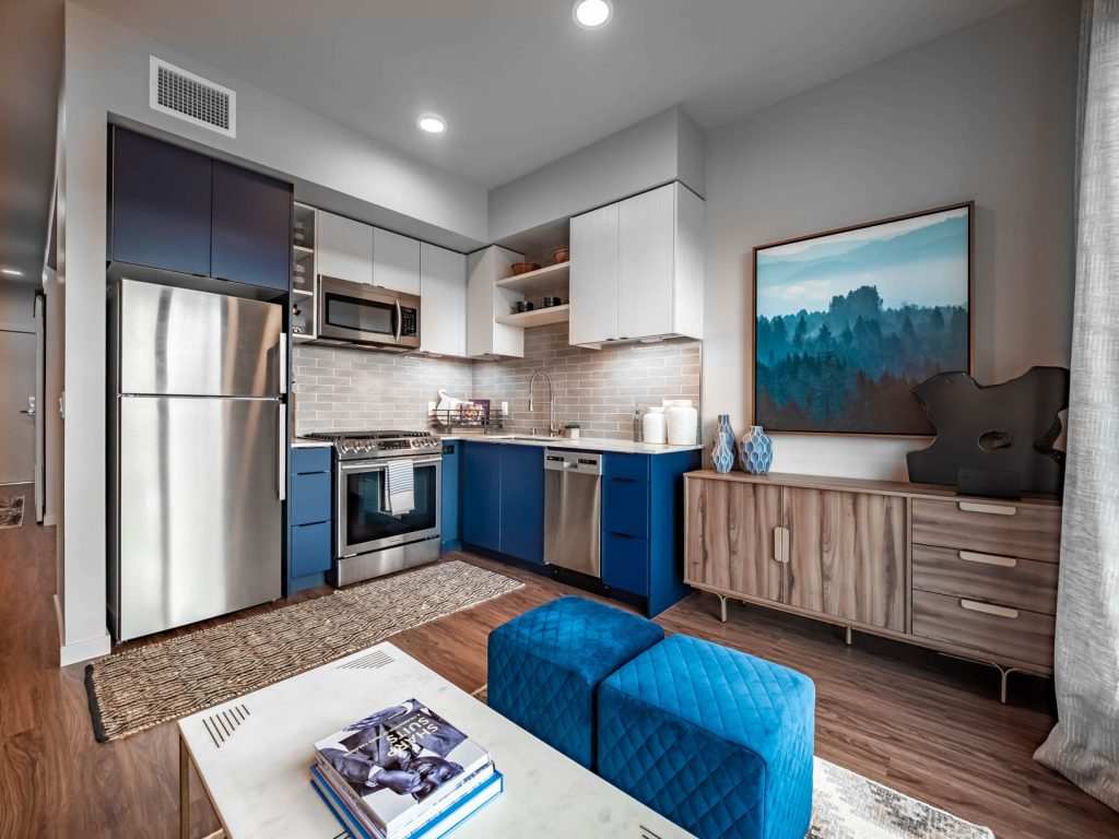 Furnished L-shaped apartment kitchen and living area with wood flooring, stainless steel appliances, two-tone cabinets, and tile backsplash.