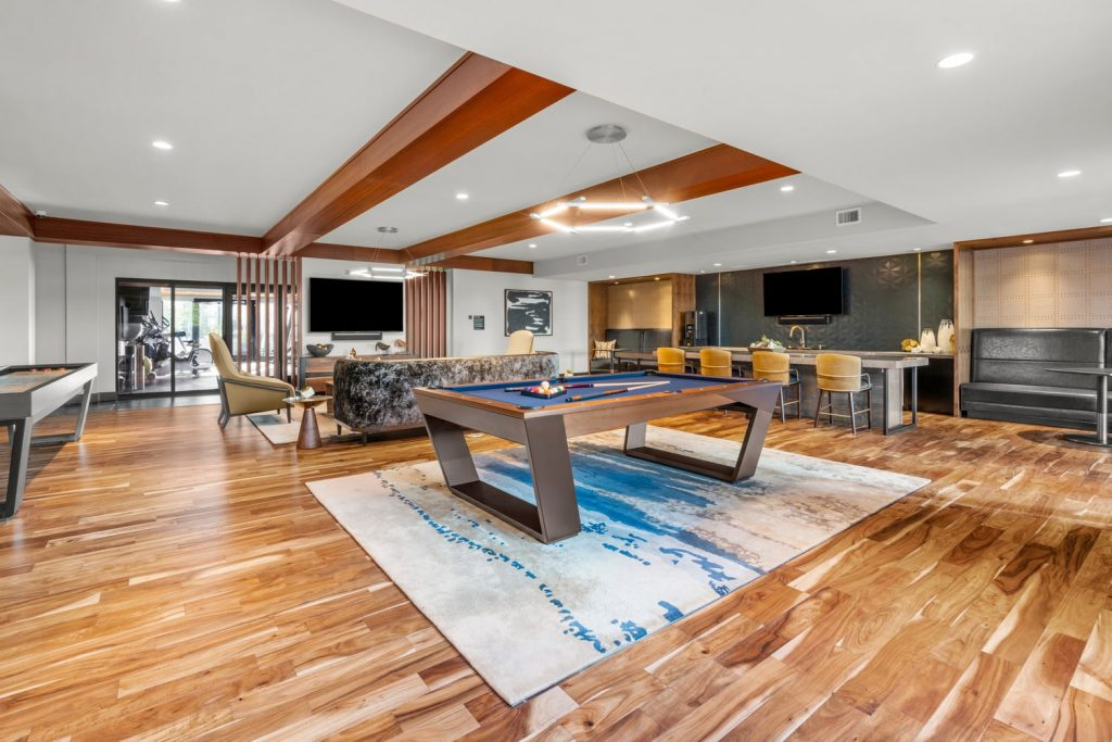Club and games room with billiards table, shuffleboard, lounge seating, wall mounted TV's, and a kitchenette with island bar seating.
