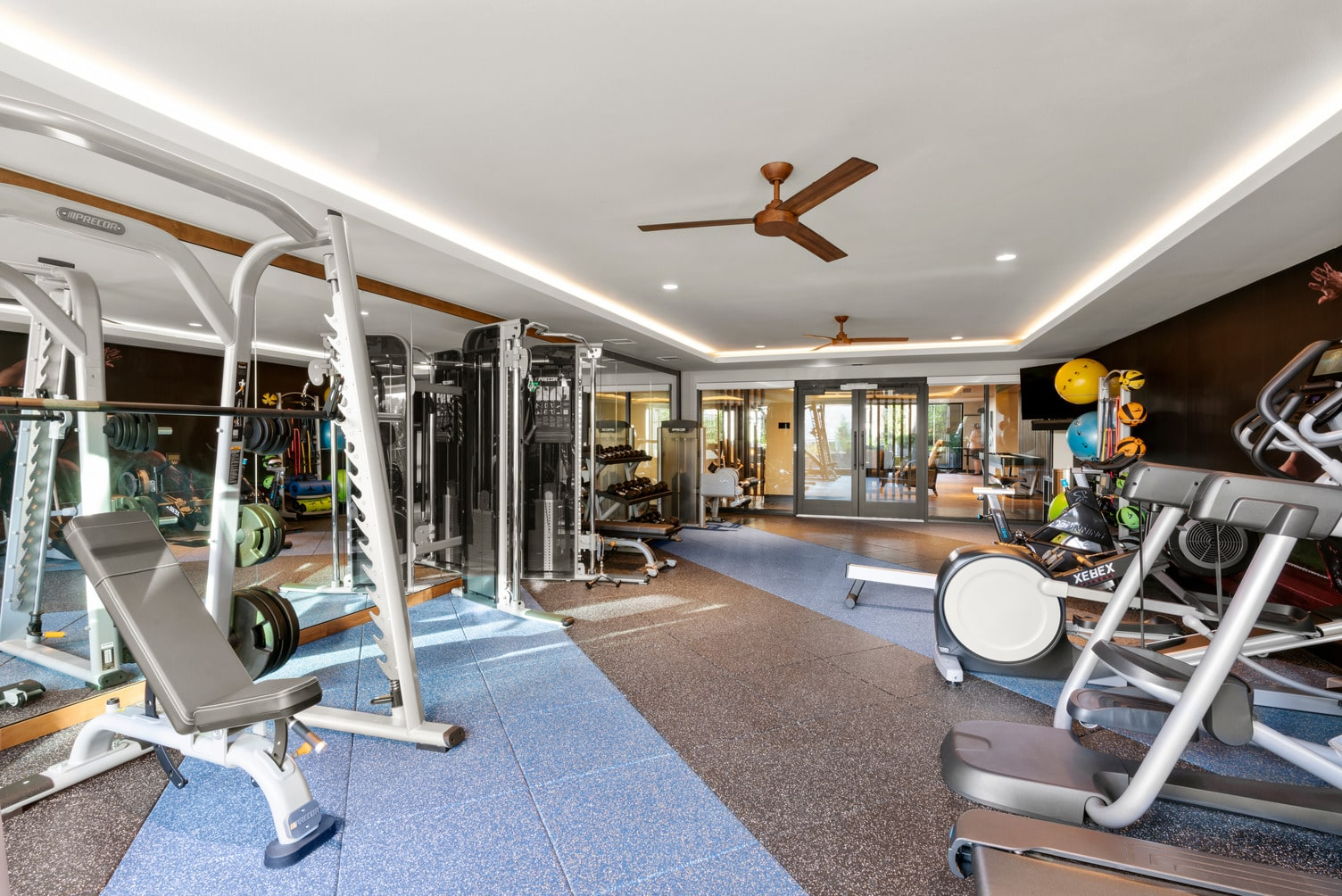 Fitness center with treadmills, ellipticals, various weight machines, free weights, yoga and medicine balls, a mounted TV, and a large floor-to-ceiling wall mirror.