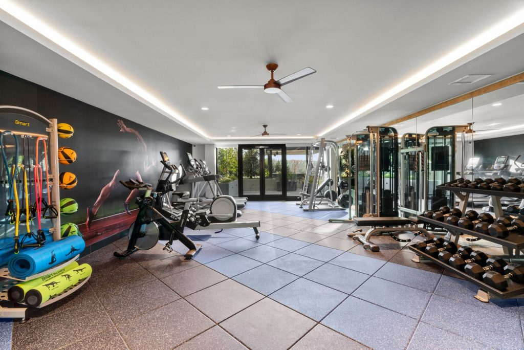 Fitness center with treadmills, ellipticals, various weight machines, free weights, yoga mats, medicine balls, a large floor-to-ceiling wall mirror opposite of a wall mural.