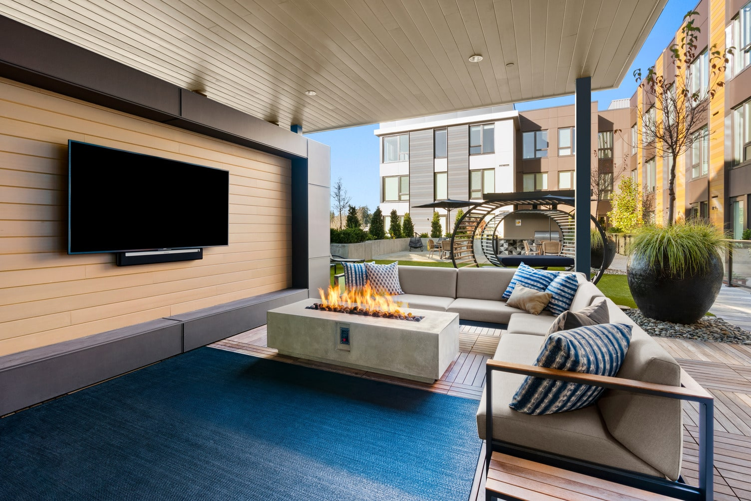 Outdoor courtyard featuring patio and grass areas with lounge seating, dining tables with umbrella coverings, and a covered grill.