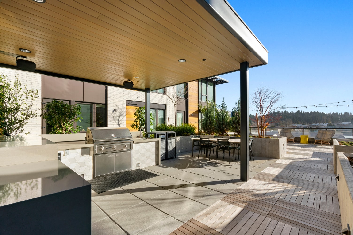 Covered outdoor grill area with dining table, raised planters, and string lighting.