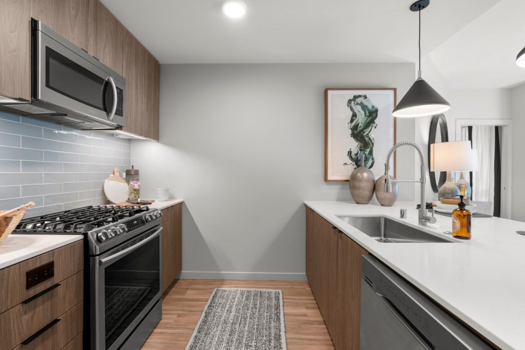 Apartment parallel style kitchen with wood flooring, stainless steel appliances, a gas stovetop, under-mounted single basin sink, tile backsplash, and hanging and recessed lighting.