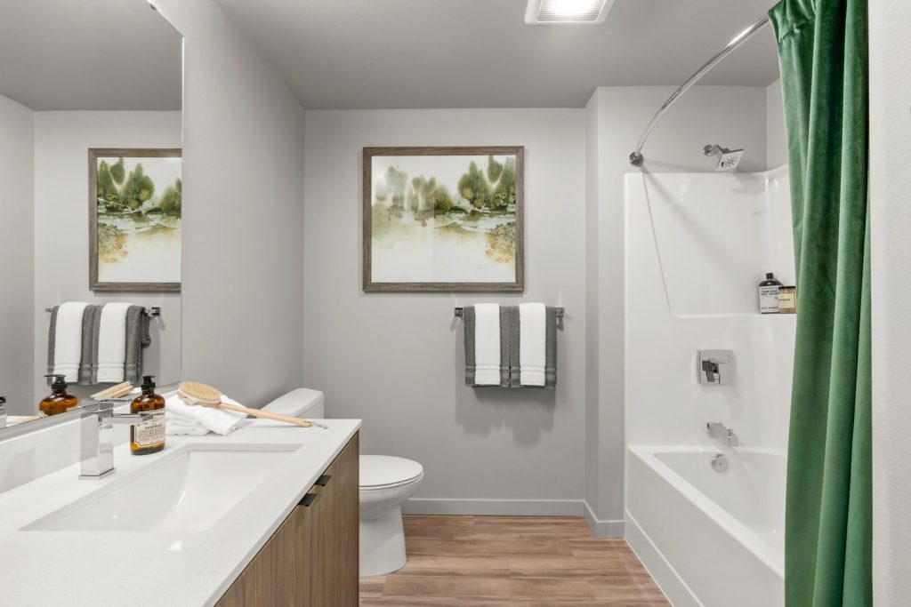 Apartment bathroom with wood flooring, an under-mounted sink, large wall mirror, and a shower and bathtub combo with curved shower rod.