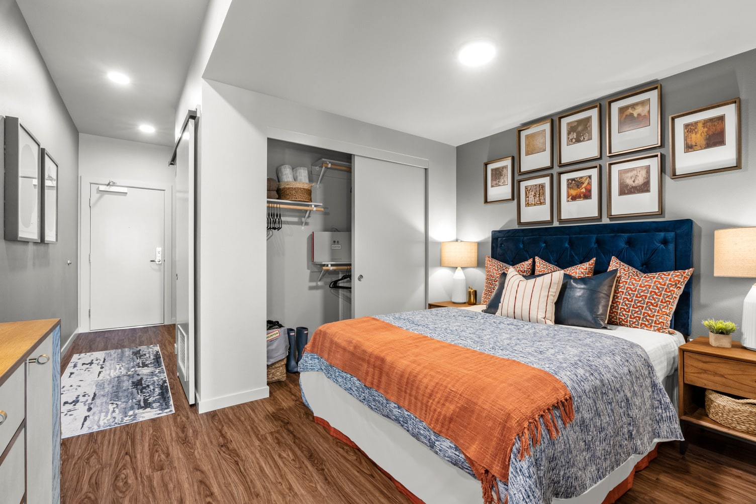 Furnished studio apartment bedroom area with wood flooring, sliding barn style door, and a closet.