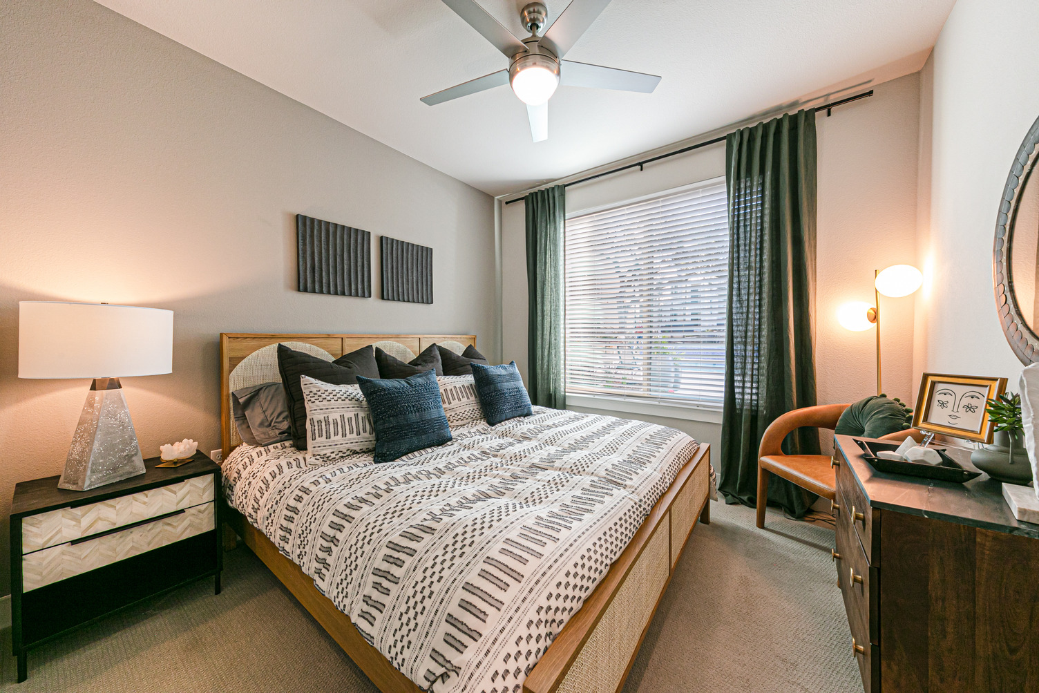Model apartment bedroom with carpeting, ceiling fan, queen bed, and large window with blinds