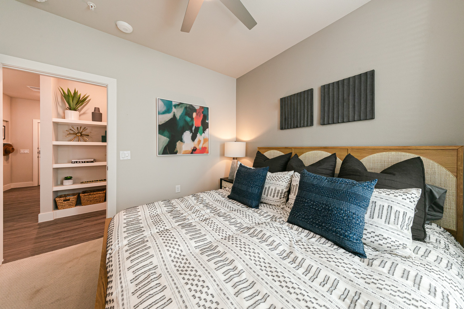 Alternate view of model apartment bedroom with carpeting, ceiling fan, queen bed, and large window with blinds