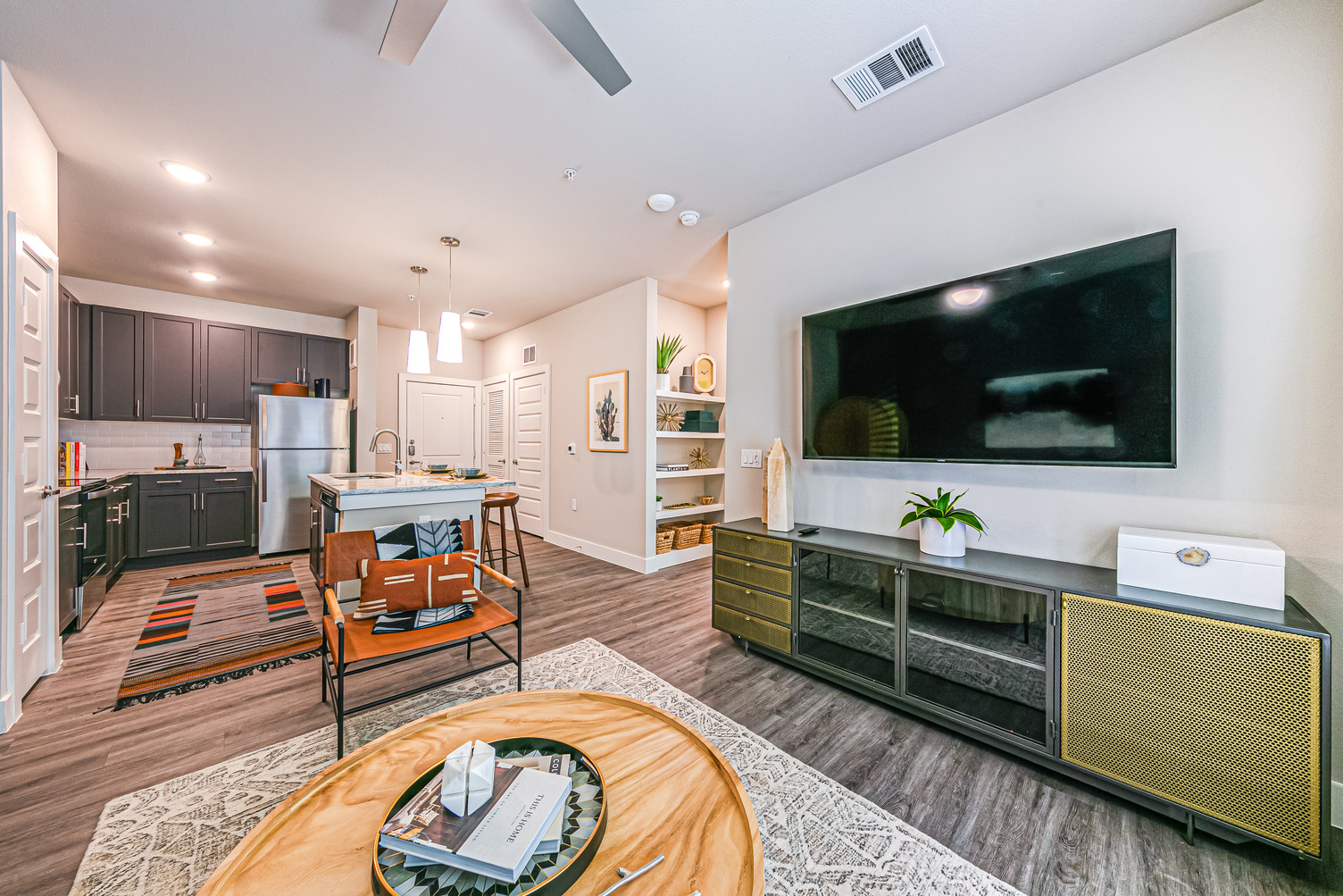 Model apartment with large TV console, built-in shelving, ceiling fan, recessed pendant lighting, and kitchen with island