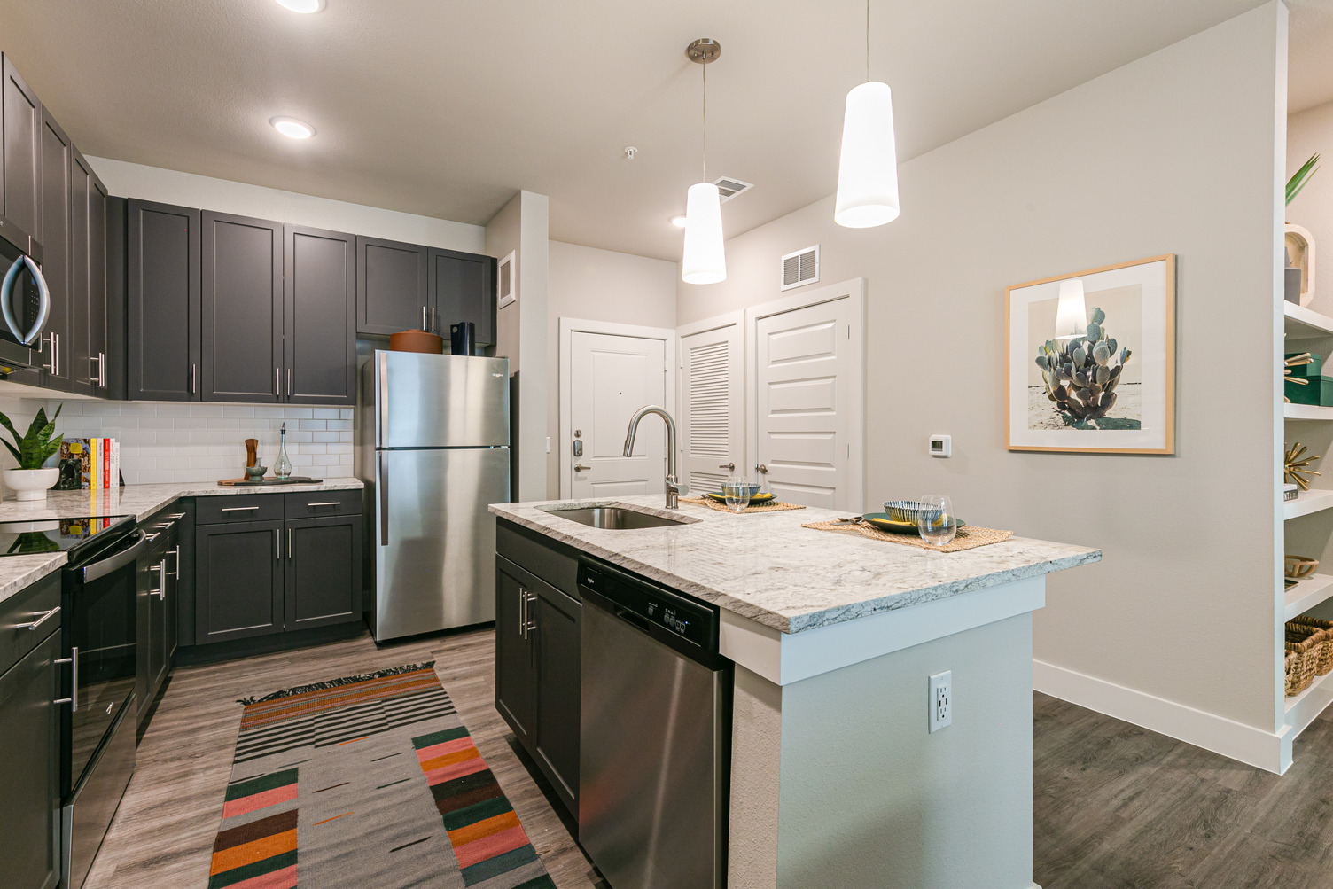 Model apartment kitchen with dark cabinets, quartz countertops, stainless steel appliances, and island with sink and dishwasher
