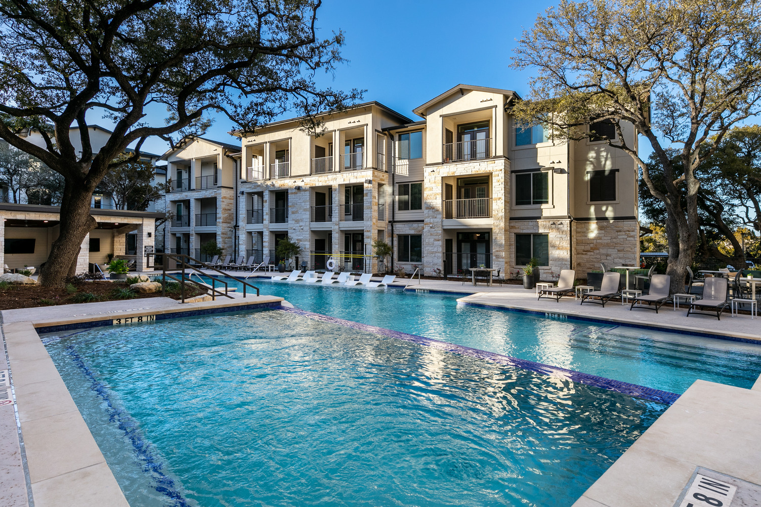 Resort-style pool courtyard with seating throughout and landscaping