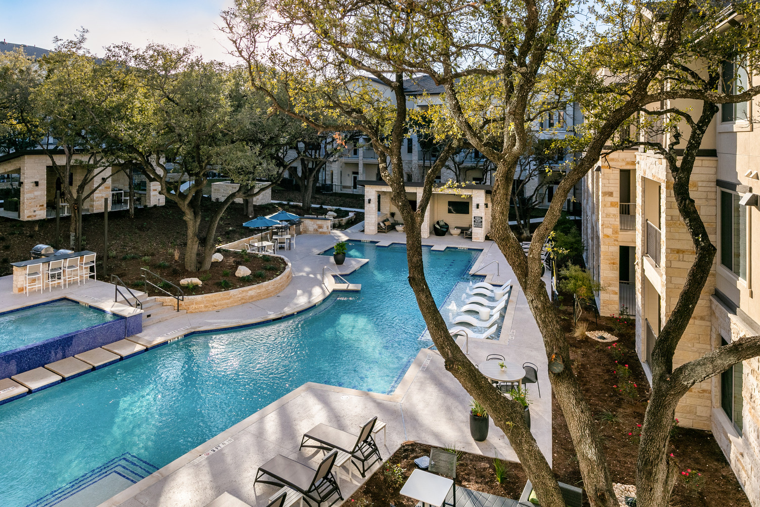 Resort-style community swimming pool with chairs and covered lounging