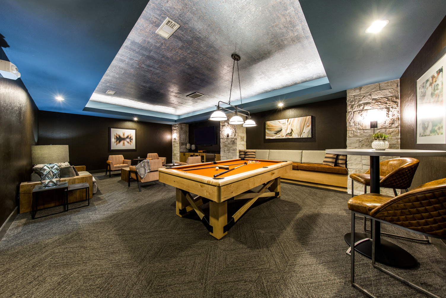 Wide view of gaming room with lounge seating and pool table