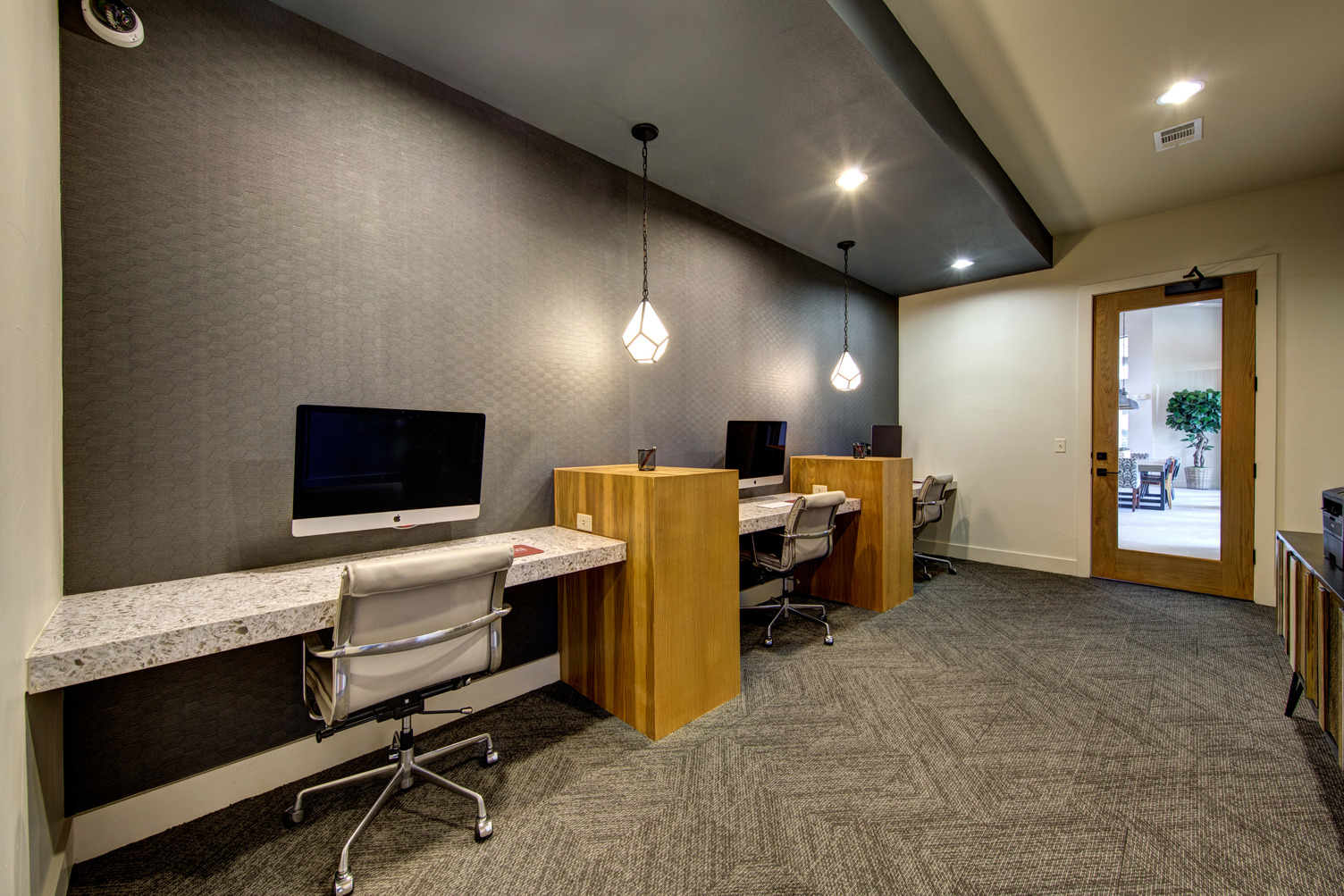 Business center with swivel chairs, three workstations with iMac, and door leading to courtyard