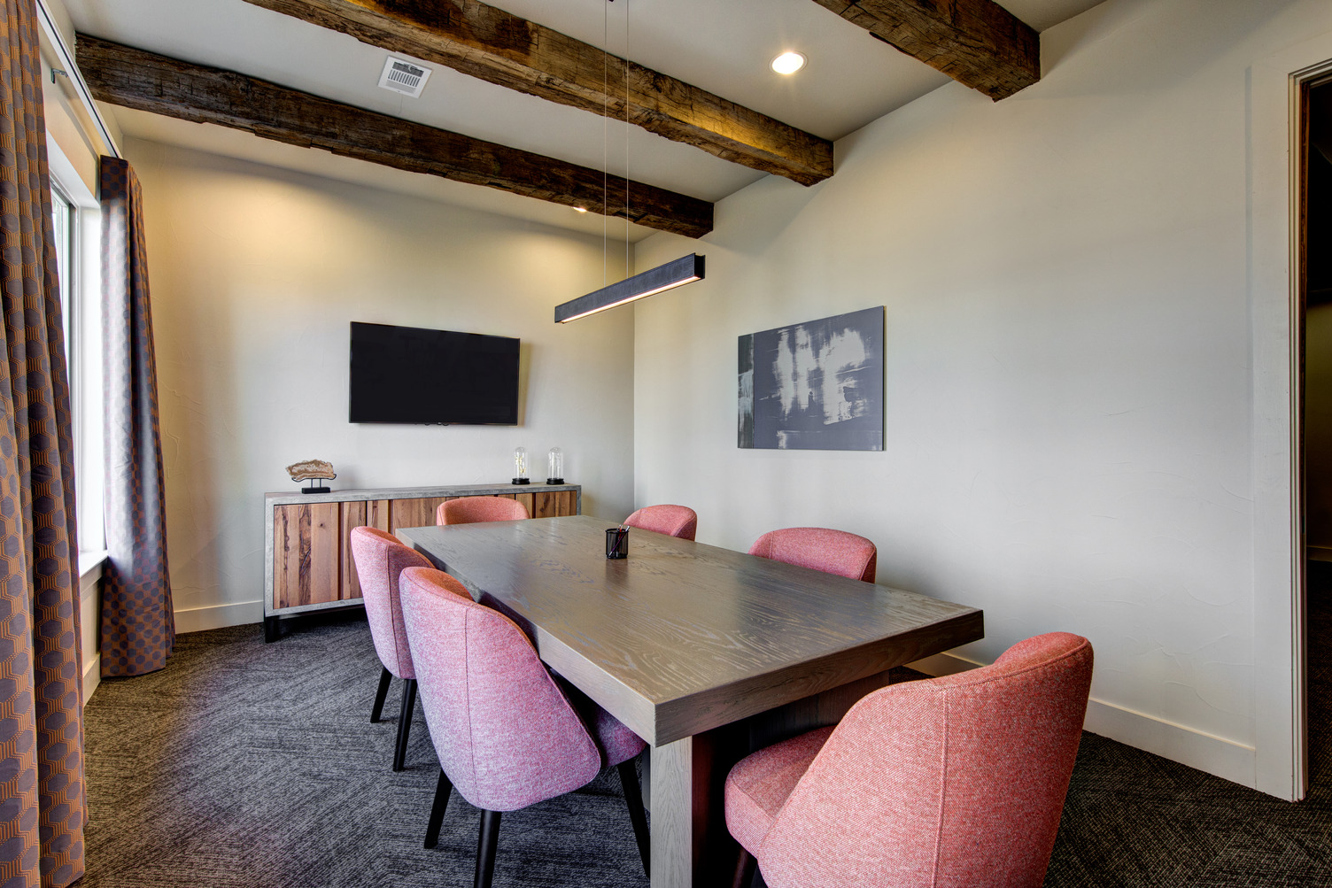 Conference room with large meeting table and wall mounted TV