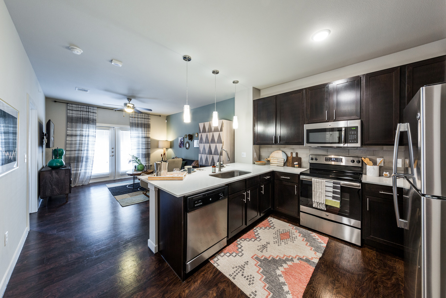 Model apartment with dark wood flooring, dark cabinets, and stainless steel appliances with pendant lighting over quartz counters