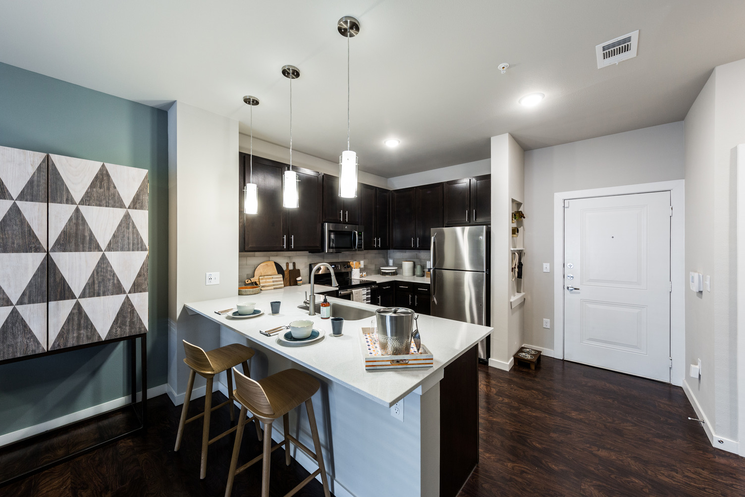 Model apartment kitchen with barstool seating, undermount sink, and dark kitchen cabinets