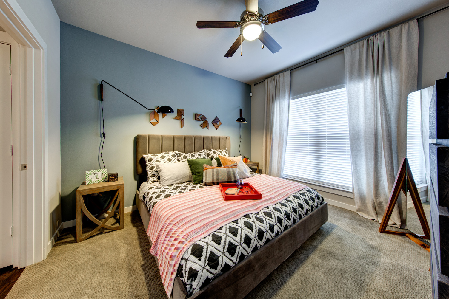 Model apartment bedroom with queen bed, ceiling fan, and carpeting