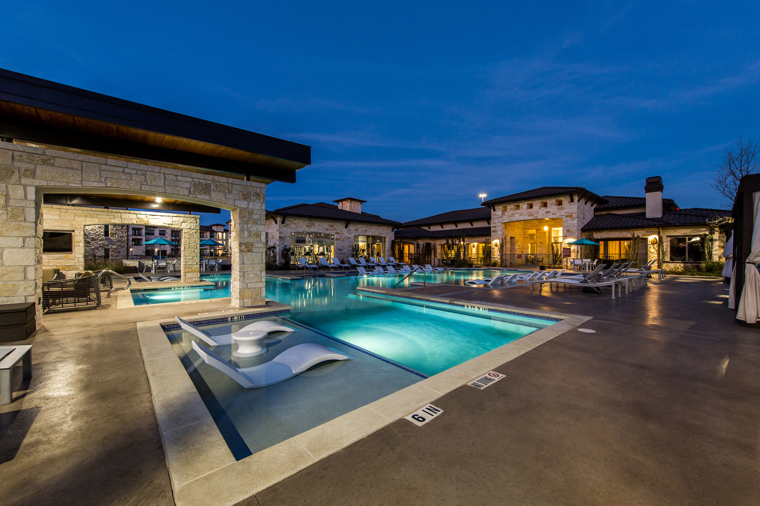 Evening view of resort-style swimming pool courtyard with lounge seating and landscaping
