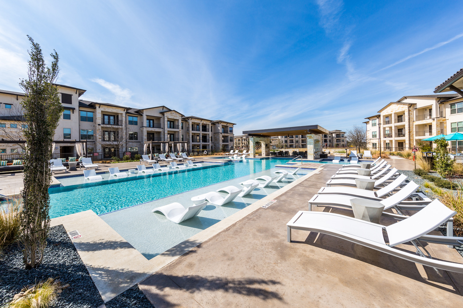 Swimming pool courtyard and in-pool loungers and additional seating