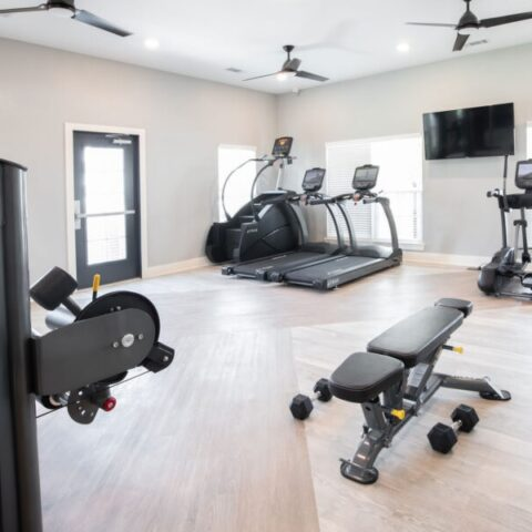 fitness center with equipment and tv's