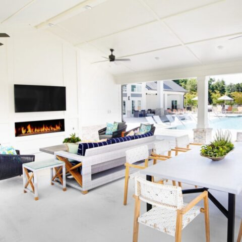 outdoor pool lounge with tvs, fireplace, and seating